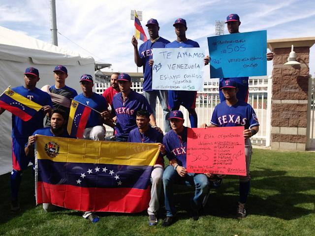 Texas Rangers baseball players pose for a photo in support of friends and family members of teammates in Venezuela including shortstop Elvis Andrus, front left, pitcher Yu Darvish, standing second from left, and third baseman Adrian Beltre, standing third from left, Saturday, Feb. 22, 2014, Surprise, Ariz. Political violence is blamed for at least eight deaths and more than 100 injuries since Feb. 12 in Venezuela, home to 63 players who were on opening day rosters at the beginning of the 2013 season. (AP Photo/Stephen Hawkins)