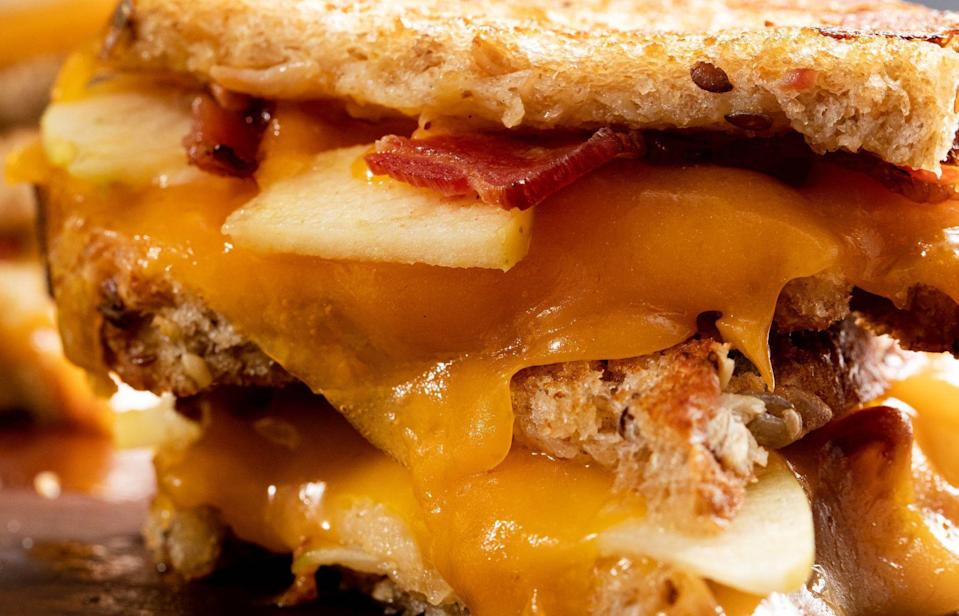 """<p>Sharp cheddar cheese pairs remarkably well with some sweetness from apples and saltiness from bacon in this jazzed-up version of your everyday grilled cheese sandwich.</p> <p><a href=""""https://www.thedailymeal.com/best-recipes/maple-apple-grilled-cheese?referrer=yahoo&category=beauty_food&include_utm=1&utm_medium=referral&utm_source=yahoo&utm_campaign=feed"""" rel=""""nofollow noopener"""" target=""""_blank"""" data-ylk=""""slk:For the Maple Apple Grilled Cheese recipe, click here."""" class=""""link rapid-noclick-resp"""">For the Maple Apple Grilled Cheese recipe, click here.</a></p>"""