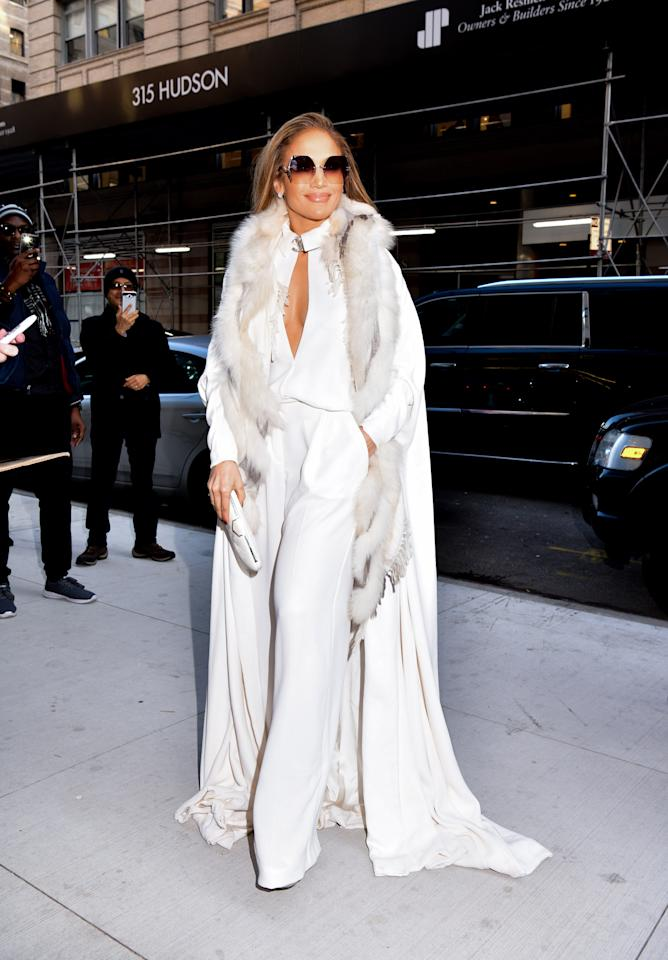 "<p>Lopez opted for a head-to-toe white ensemble by Stéphane Rolland on Tuesday Dec. 11 as she arrived for her appearance on ""Watch What Happens Live"" in Manhattan. Paired with a fur stole and Jimmy Choo clutch, J.Lo added some added bling to her look with her Chanel brooch. </p>"