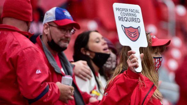 PHOTO:  An usher walks through the aisles and carries a sign reminding fans to wear their mask during the seventh inning of the home opener against the Milwaukee Brewers at Busch Stadium in St Louis, Mo., April 8, 2021. (Jeff Curry/Getty Images, FILE)