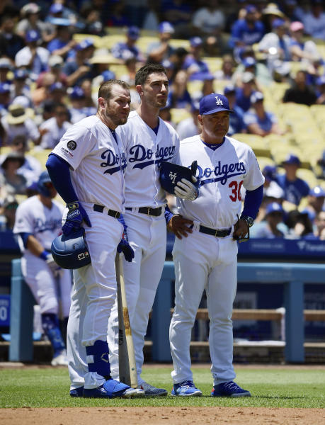 Los Angeles Dodgers Max Muncy, left, stand with Cody Bellinger, center, and manager Dave Roberts after Bellinger hit a fan with a foul ball during the first inning of a baseball game against the Colorado Rockies Sunday, June 23, 2019, in Los Angeles. (AP Photo/Mark J. Terrill)