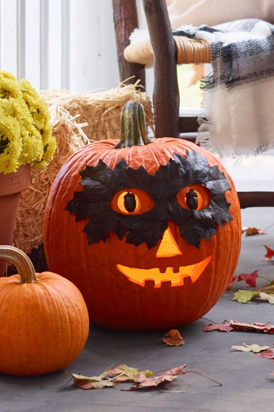 <p>Don't worry, this masked pumpkin won't steal your candy. His leaf mask is only there to help keep the mystery alive!<strong><br></strong></p><p><strong>Make the Masked Pumpkin:</strong> Paint eight real or artificial leaves with black spray paint; let dry. Layer leaves into a mask shape; hot-glue together. Cut eyeholes in mask. Trace eyeholes onto large orange pumpkin; carve. Glue black-painted acorns to straight pins, then push into eyeholes for pupils. Secure leaf mask to pumpkin with hot glue.</p>