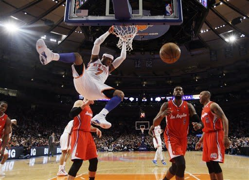 New York Knicks' Carmelo Anthony (7) dunks the ball as Los Angeles Clippers' DeAndre Jordan chases down the ball during the first half of an NBA basketball game, Wednesday, April 25, 2012, in New York. (AP Photo/Frank Franklin II)