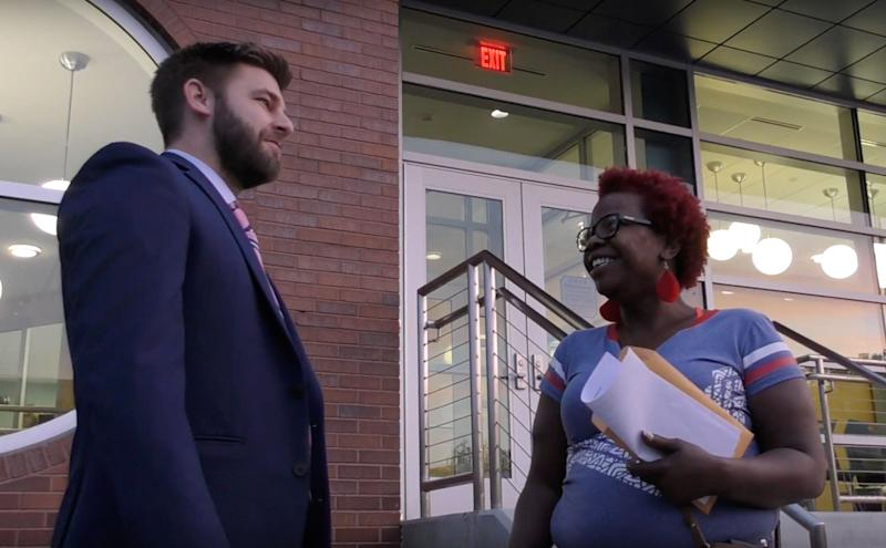 Angelia Bradley and her lawyer, Nathaniel Carroll, stand outside Ferguson's Municipal Court building. Bradley performed community service in lieu of fines she faced for various traffic tickets.