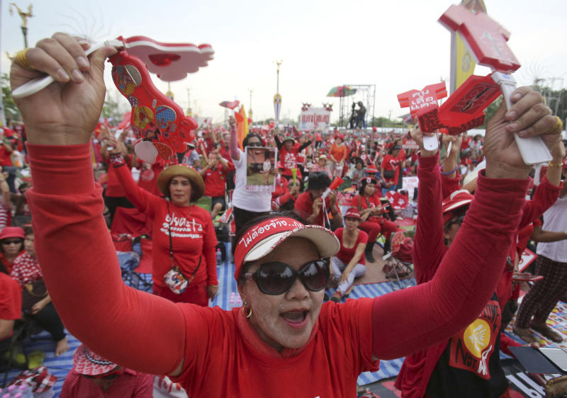 Pro-government Red Shirt members shake clapping tools during a rally in Bangkok, Thailand, Saturday, April 5, 2014. Supporters of Thailand's beleaguered prime minister are holding a major rally Saturday, a move aimed at countering months of anti-government protests and an increasing spate of legal challenges that could bring down Yingluck Shinawatra's administration. (AP Photo/Sakchai Lalit)
