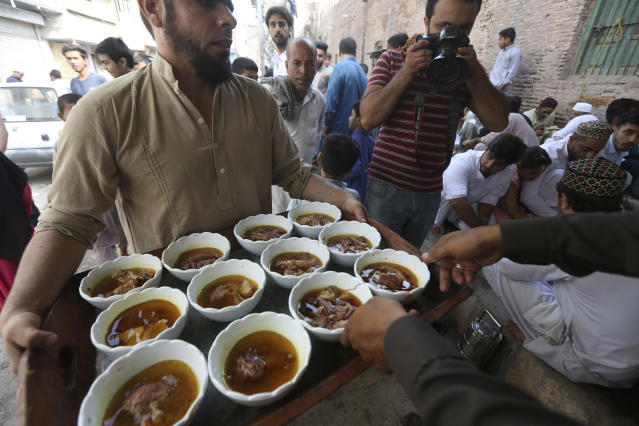 <p>A man distributes meal to people on the first day of Eid al-Adha, or Feast of Sacrifice, in Karachi, Pakistan, Saturday, Sept. 2, 2017. (Photo: Fareed Khan/AP) </p>