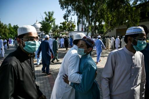 Muslims exchange greetings after offering Eid al-Fitr prayers despite concerns over the spread of the COVID-19 coronavirus at the Eidgah Sharif Darbar in Rawalpindi