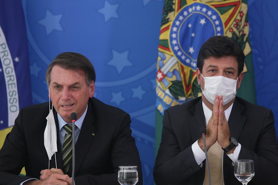 BRASILIA, BRAZIL - MARCH 18: (L-R) President of Brazilian Jair Bolsonaro and Health Minister Luiz Henrique Mandetta wear protective masks during a press conference about government plans and measures about the Coronavirus (COVID-19) Outbreak in Brazil, at the Planalto Palace on March 18, 2020 in Brasilia, Brazil. (Photo by Andre Coelho/Getty Images)