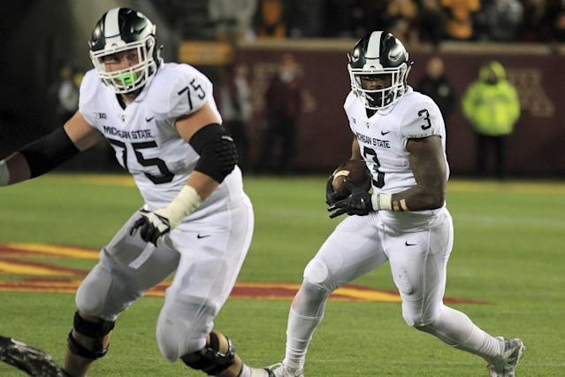 Michigan State running back L.J. Scott (3) runs with blocking from teammate guard Kevin Jarvis (75) against Minnesota in the third quarter of an NCAA college football game Saturday, Oct. 14, 2017, in Minneapolis. Michigan State defeated Minnesota 30-27. (AP Photo/Andy Clayton-King)