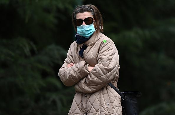 A woman wearing a face mask walks through the city in Melbourne, Australia.
