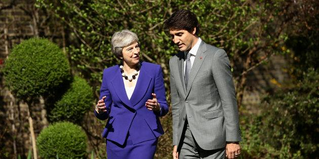 Britain's Prime Minister Theresa May speaks with Prime Minister Justin Trudeau in the gardens of 10 Downing Street in London on April 18, 2018.