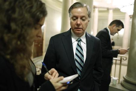 U.S. Senator Graham talks to a reporter as he arrives for a Republican Senate caucus meeting at the U.S. Capitol in Washington