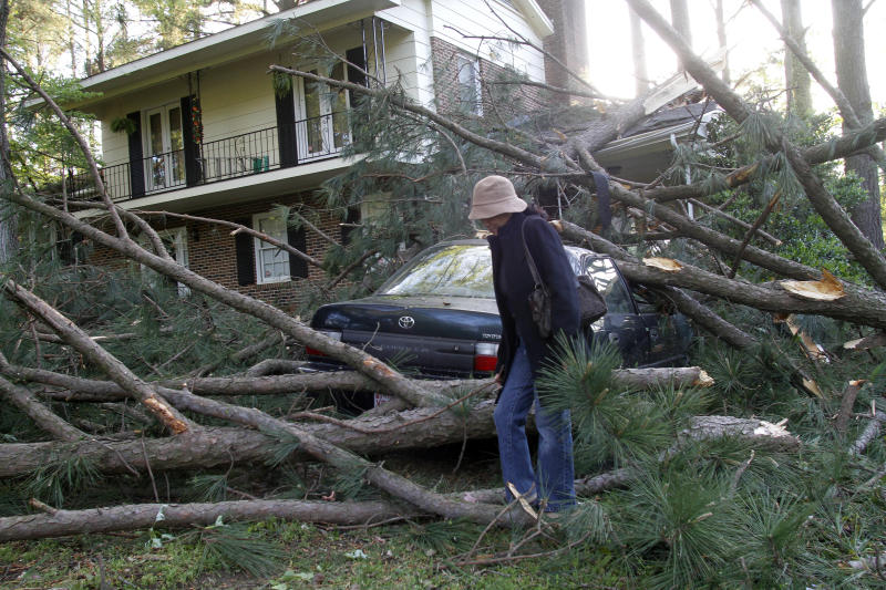 """A lady inspectrs  her home and car in Raleigh, N.C., Sunday, April 17, 2011.  Homes and businesses were badly damaged Saturday by a severe storm system that whipped across North Carolina, bringing flash floods, hail and reports of tornadoes from the western hills to the streets of Raleigh. In the Lee County town of Sanford, a Lowe's store was smashed by the storm. """"The Lowe's Home Improvement has been flattened,"""" said Monica Elliott, who works at the nearby Brick City Grill. """"It's totally destroyed."""" (AP Photo/Jim R. Bounds)"""