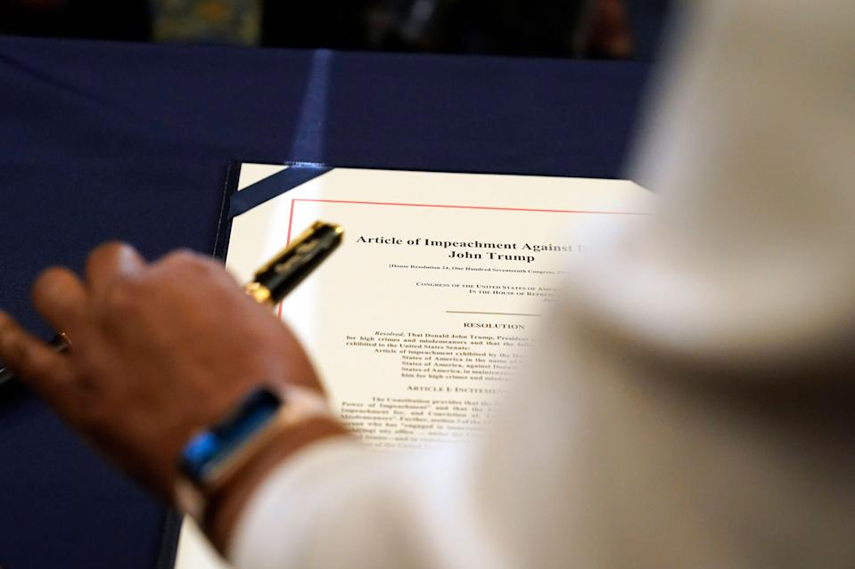Staff member Latrice Powell placed the article of impeachment against Trump on a table for Pelosi to sign. (Alex Brandon/Associated Press)