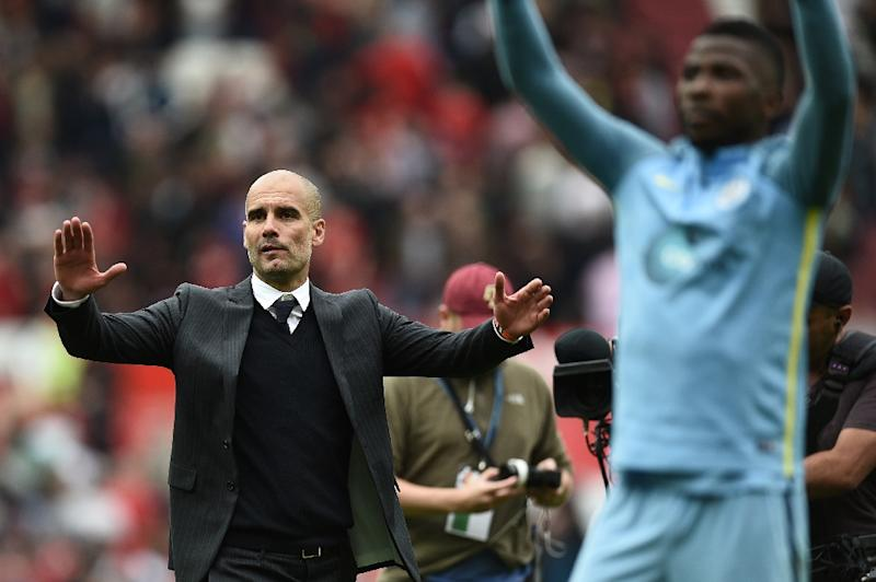 Manchester City's manager Pep Guardiola and his players celebrate after defeating Manchester United in their English Premier League match at Old Trafford, on September 10, 2016