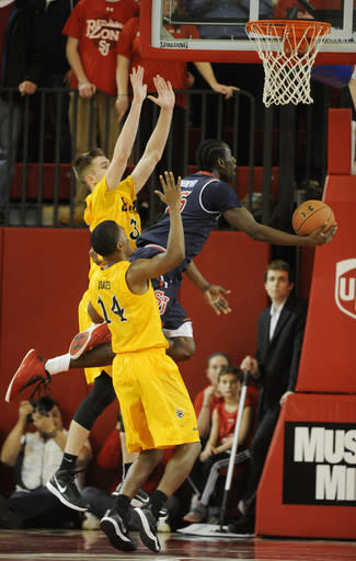 St. John's guard Sir'Dominic Pointer (15) drives for the basket between Long Beach State guard's Anson Moye (3) and Branford Jones (14) during the first half of an NCAA college basketball game Monday, Dec. 22, 2014 in New York. (AP Photo/Kathy Kmonicek)