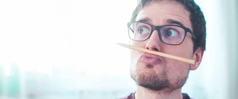 Young Caucasian man is fooling around and home, pencil trapped between nose and lips