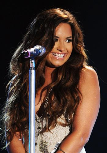 <p>Demi Lovato gets all lovey-dovey with her fans as she performs onstage during the 2011 VH1 Do Something Awards on August 14.</p>