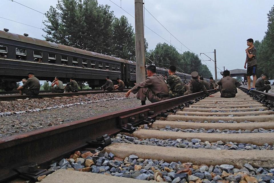 <p>Korean soldiers rest on the train tracks. It is photos like these, which show soldiers taking some time out, that the state has the biggest problem with entering worldwide media. (Getty) </p>