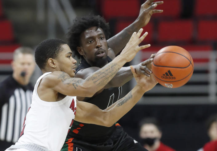Miami's Nysier Brooks (3) knocks the ball from the hands of North Carolina State's Shakeel Moore (2) during the second half of an NCAA college basketball game at PNC Arena in Raleigh, N.C., Saturday, Jan. 9, 2021. (Ethan Hyman/The News & Observer via AP)