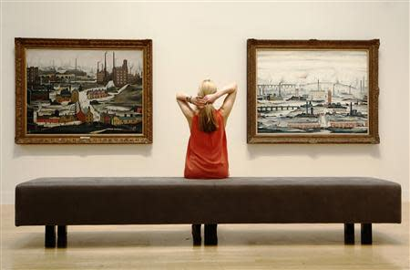 A file photograph shows a Tate employee posing for a photograph with works by British artist L.S.Lowry at Tate Britain in London
