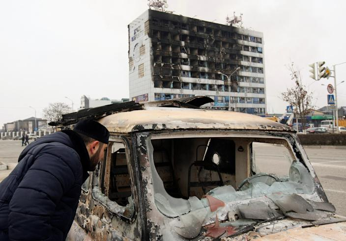 A man looks into a burnt-out car near the Press House building, a local media agency, in the Chechen capital Grozny, in December 2014.
