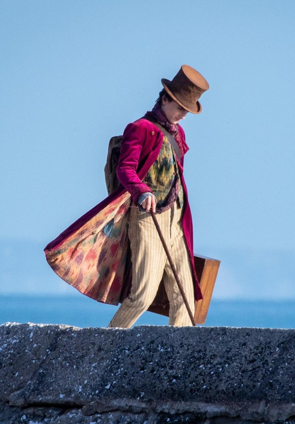 <p>Shoutout to the breeze in England for revealing the colorful underside of Timothée's Wonka coat. As for the layers underneath, he's rocking a pink and purple patterned scarf tucked into a black and mustard button-up waistcoat.</p>