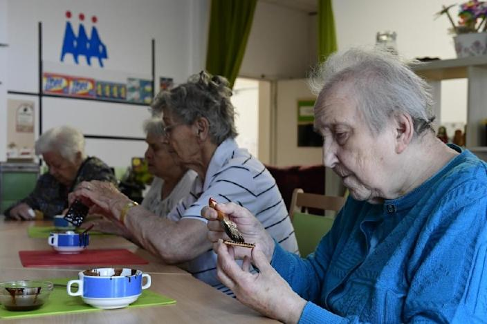 Making a chocolate biscuit cake, popular in communist East Germany, is one way of helping revive memories as part of the innovative treatment for dementia patients (AFP Photo/)