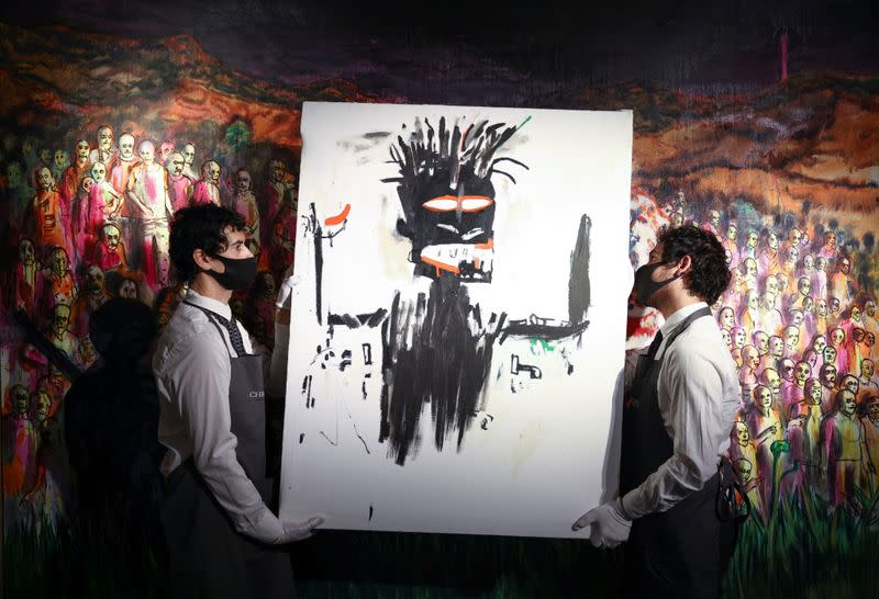 Gallery assistants hold artwork titled 'Self Portrait' by Jean-Michel Basquiat during a photocall at Christie's auction house, in London