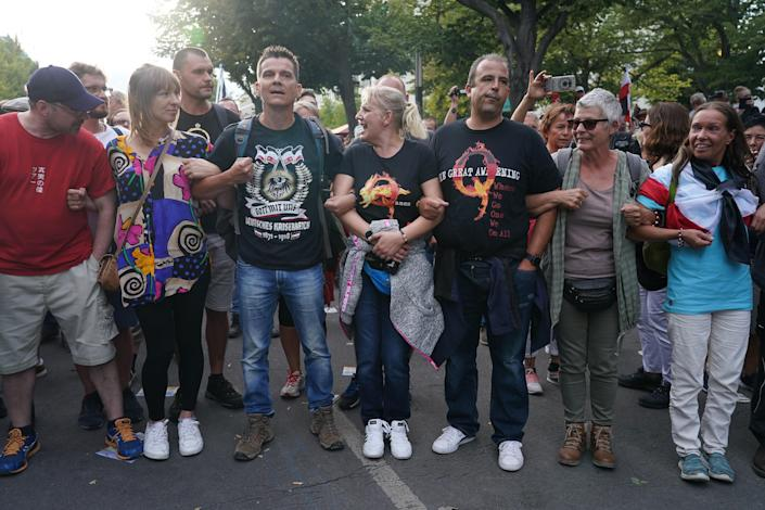 BERLIN, GERMANY - AUGUST 29: A man wearing a right-wing t-shirt and a couple wearing QAnon shirts face off against riot police on Unter den Linden avenue during protests against coronavirus-related restrictions and government policy on August 29, 2020 in Berlin, Germany. Tens of thousands of people from a wide spectrum, including coronavirus skeptics, conspiracy enthusiasts, hippies, right-wing extremists, religious conservatives and others converged on Berlin to attend the protests. City authorities had banned the protests, citing the flouting of social distancing by participants in a similar march that drew at least 17,000 people a few weeks ago, but a court overturned the ban. / Credit: / Getty Images