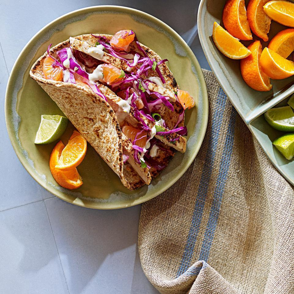 <p>This spicy chicken taco recipe gets fresh orange flavor from both the crema and crunchy slaw toppings. Serve with tortilla chips and ice-cold beer.</p>