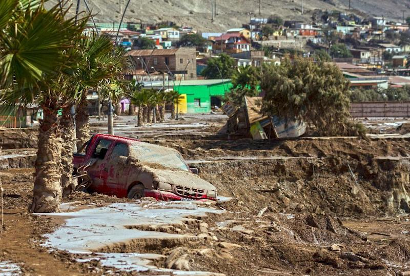 A car remains in the mud at an area which was flooded in Chanaral, after heavy rainfall caused the overflowing of the Copiapo river and the flooding of parts of the city in northern Chile, on April 1, 2015. At least 23 people were killed in flash floods that hit a normally arid region of northern Chile last week, and 53 remain missing, authorities said today. AFP PHOTO/PATRICIO MIRANDA (AFP Photo/Patricio Miranda)
