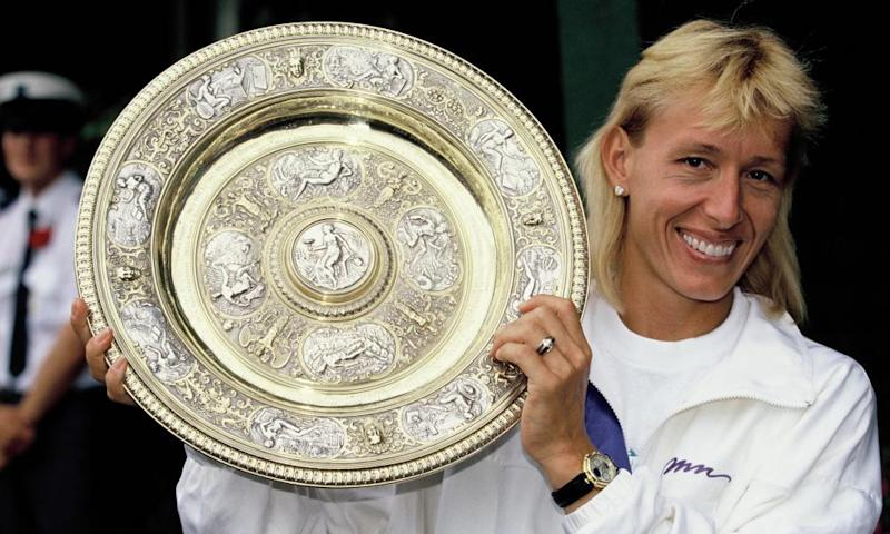 Martina Navratilova shows off her Wimbledon trophy in 1990.