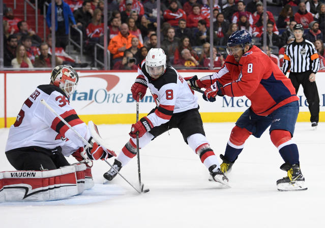 Washington Capitals left wing Alex Ovechkin (8), of Russia, battles for the puck against New Jersey Devils goaltender Cory Schneider (35) and defenseman Will Butcher (8) during the second period of an NHL hockey game Saturday, April 7, 2018, in Washington. (AP Photo/Nick Wass)
