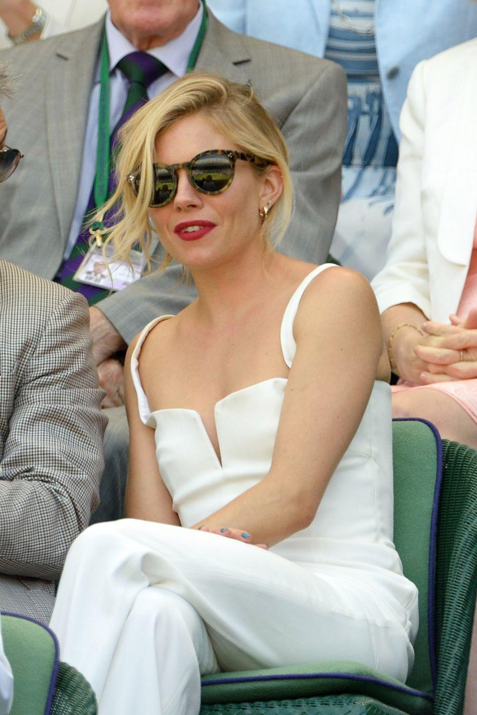 <p><strong>2015</strong> Once again, Sienna Miller looked chic in a white Galvan jumpsuit as she sat courtside.</p>