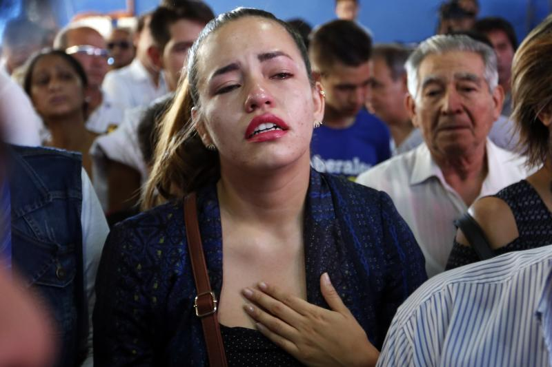 A relative cries as she attends the wake of Rodrigo Quintana, a member of the Authentic Radical Liberal Party who was killed in an incident at party's headquarters away from congress at the party's headquarters on Friday, in Asuncion, Paraguay, Saturday, April 1, 2017. Clashes erupt between police and protesters outside Paraguay's congress, with demonstrators setting fires around the building after a majority of senators carry out what some was called an irregular vote to allow presidential re-election. (AP Photo/Jorge Saenz)