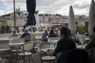 People enjoy refreshments at a restaurant, in Marseille, southern France, Sunday Sept. 27, 2020. As restaurants and bars in Marseille prepared Sunday to shut down for a week as part of scattered new French virus restrictions, Health Minister Olivier Veran insisted that the country plans no fresh lockdowns. (AP Photo/Daniel Cole)