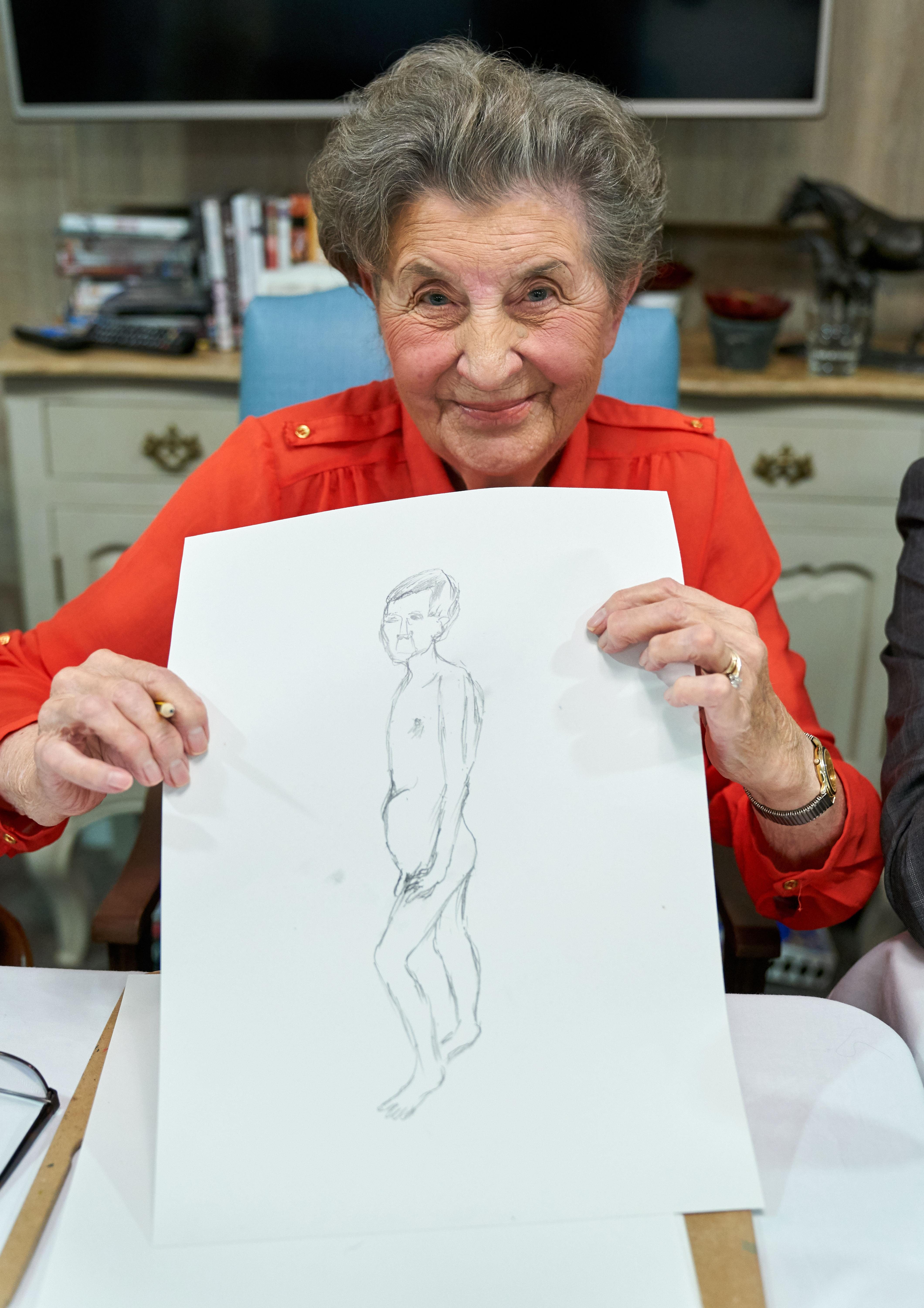 A care home resident reveals her finished pencil sketch. [Photo: Simon Jacobs]