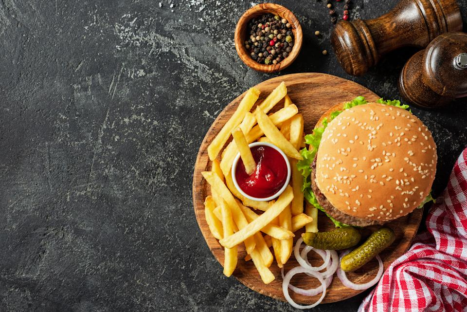 Burger and fries on wooden board on dark stone background. Homemade burger or cheeseburger, french fries and ketchup. Tasty sandwich. Top view with copy space for text