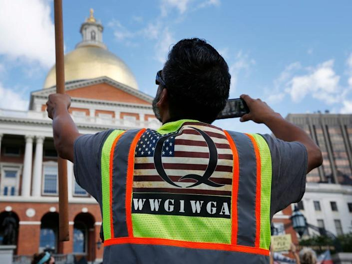 """A man wearing a QAnon vest held a flag during a No Mandatory Flu Shot Massachusetts rally held outside of the State House in Boston on Aug. 30, 2020. <p class=""""copyright"""">Jessica Rinaldi/The Boston Globe via Getty Images</p>"""