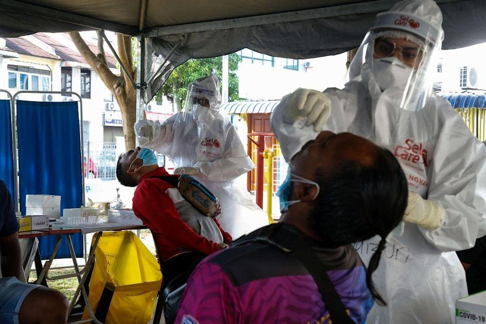 Healthcare workers collect swab samples to test for Covid-19 during a mass screening exercise in Taman Manggis, George Town August 12, 2021. — Picture by Sayuti Zainudin