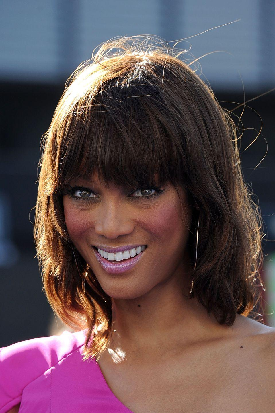"""<p>Make like model <strong>Tyra Banks</strong> and add <a href=""""https://www.goodhousekeeping.com/beauty/hair/g33267765/types-of-bangs/"""" rel=""""nofollow noopener"""" target=""""_blank"""" data-ylk=""""slk:full bangs"""" class=""""link rapid-noclick-resp"""">full bangs</a> to a long asymmetrical bob to frame the top of the face.</p>"""