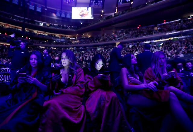 "FILE- In this Nov. 12, 2016, file photo, octagon-side models look at their cell phones between mixed martial arts bouts at UFC 205 at Madison Square Garden in New York. Our phones and apps are designed to give us short-term, feel-good rewards, so we'll use them as much as possible, at the expense of reading, enjoying the moment or simply being bored. Due in part to a backlash from customers and experts, some companies are relenting, Google, for example, plans features such as a ""wind down"" mode in its next mobile operating system, P, which will start arriving on phones in the fall. (AP Photo/Julio Cortez, File)"