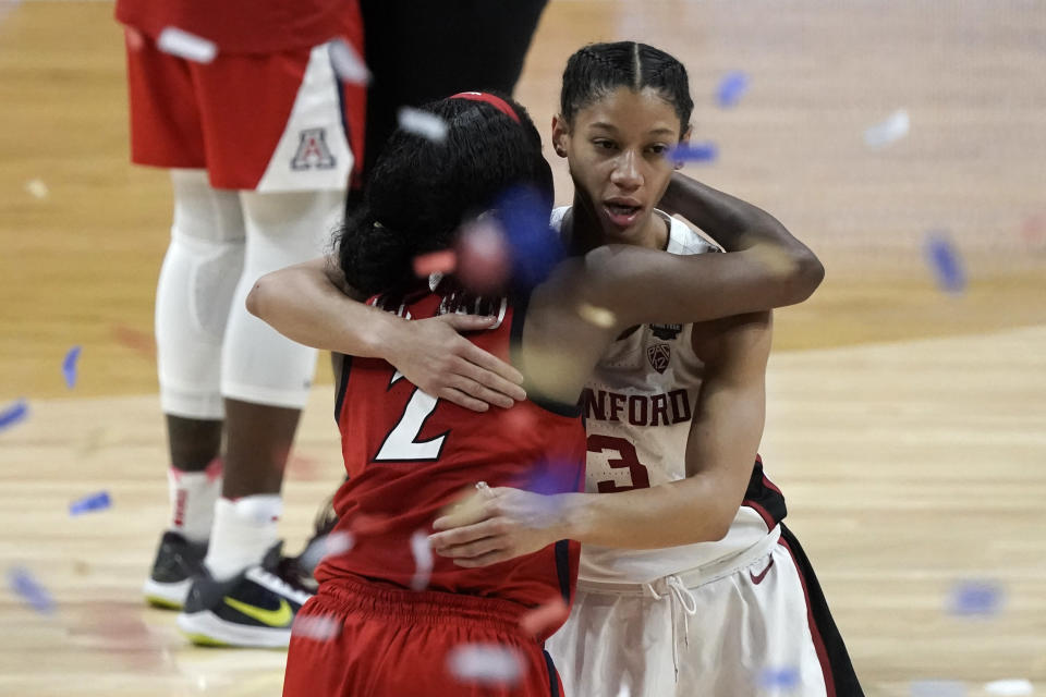 Arizona guard Aari McDonald (2) gets a hug from Stanford guard Anna Wilson (3) at the end of the championship game in the women's Final Four NCAA college basketball tournament, Sunday, April 4, 2021, at the Alamodome in San Antonio. Stanford won 54-53. (AP Photo/Morry Gash)
