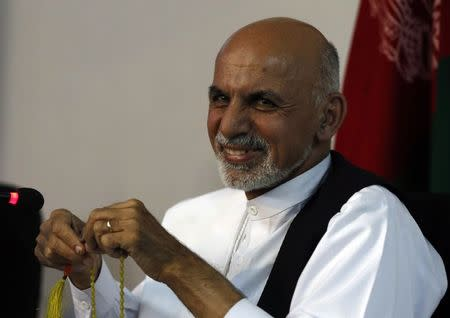 Afghan presidential candidate Ashraf Ghani Ahmadzai smiles during a news conference in Kabul
