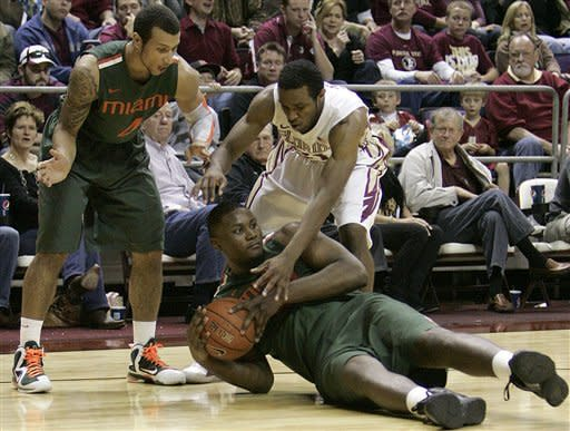 Miami's Reggie Johnson gathers up a loose ball as teammate Trey McKinney Jones, left, looks to help as Florida State's Michael Snaer comes to the defense in the second half of an NCAA college basketball game on Saturday, Feb. 11, 2012 in Tallahassee, Fla.(AP Photo/Steve Cannon)
