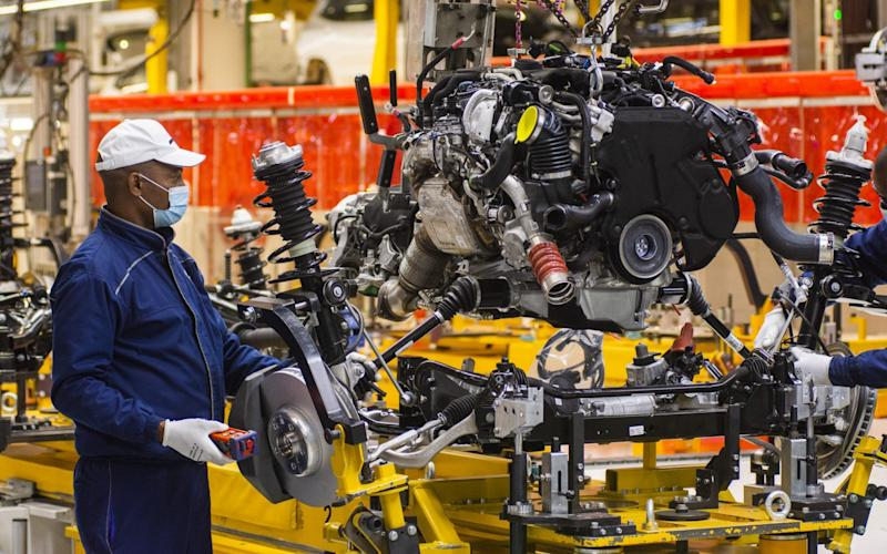 A worker wearing a protective face mask secures a suspension unit to an automobile chassis on the production line at the BMW South Africa , May 29, 2020.