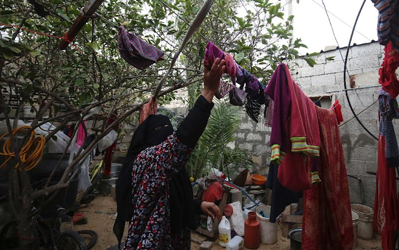 Angham Zorab removes clothes from a clothes line at their home in the southern Gaza Strip refugee camp of Khan Yunis (AFP Photo/SAID KHATIB)