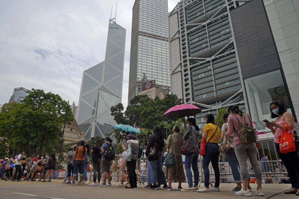 Filipino migrant workers line up at the temporary testing center for COVID-19, in Hong Kong, Saturday, May 1, 2021. The government ordered foreign domestic helpers to take COVID-19 tests after two helpers were diagnosed with a more infectious strain of the virus. (AP Photo/Kin Cheung)