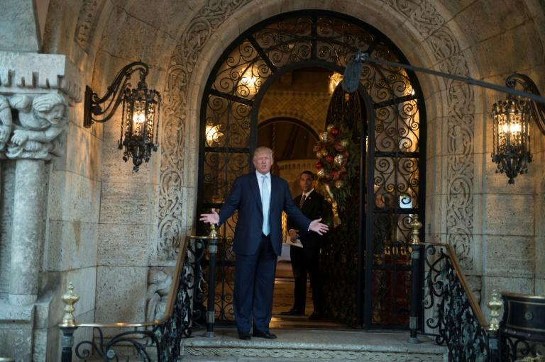 Donald Trump stands before his luxurious Florida compound, where he has spent many weekends of his young presidency